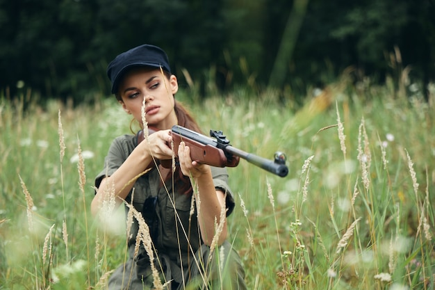 Woman with a gun outdoors in the forest and green grass