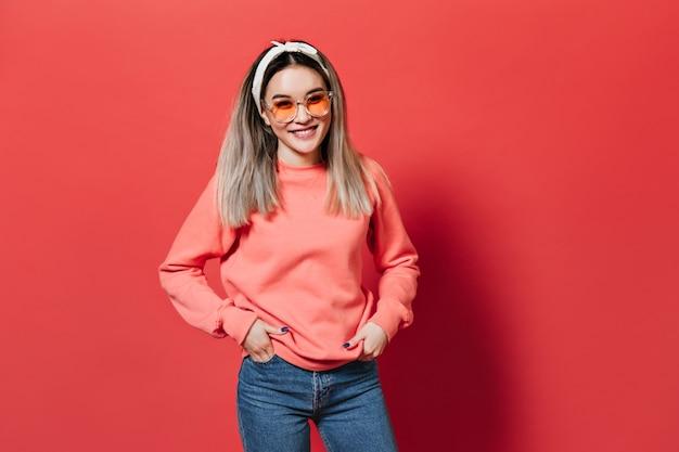 オレンジ色のメガネとスウェットシャツを着て、赤い壁にポーズをとって、ヘアバンドを持つ女性