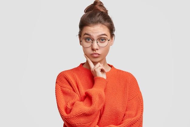 Donna con i capelli in un panino che indossa un maglione oversize