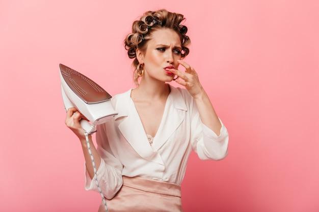 Женщина с бигуди обожгла утюг и облизывает палец