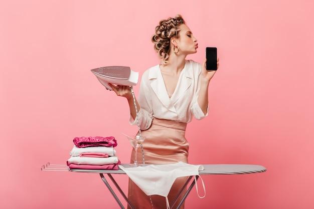 Женщина с бигуди держит утюг и целует свой смартфон