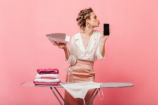 Donna con bigodini tiene il ferro e bacia il suo smartphone
