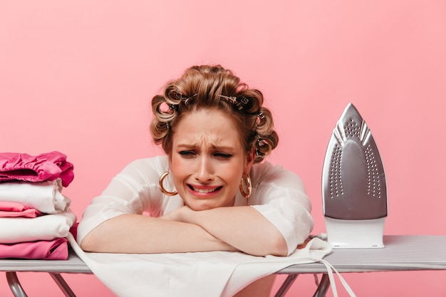 Woman with hair curlers leans on ironing board and cries