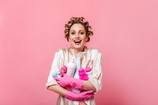 La donna con i bigodini guarda davanti con un sorriso e tiene i prodotti per la pulizia