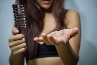 Woman with hair loss holding comb. Young girl losing hair problem health