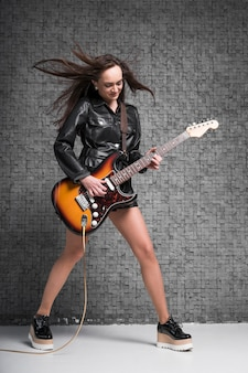 Woman with hair in the wind playing the guitar