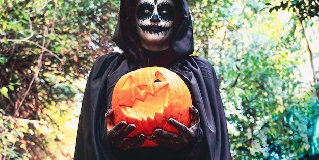 黒いフードを身に着けているハロウィーンの塗装フェイスマスクを持つ女性