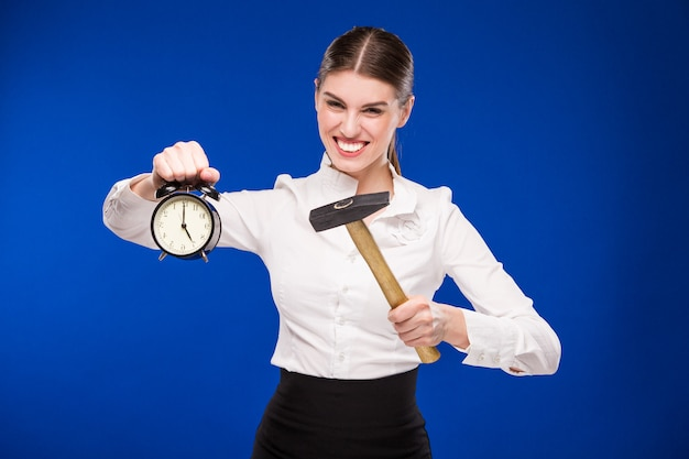 Woman with hammer and alarm clock