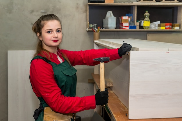 Woman with hammer constructing furniture in carpentry