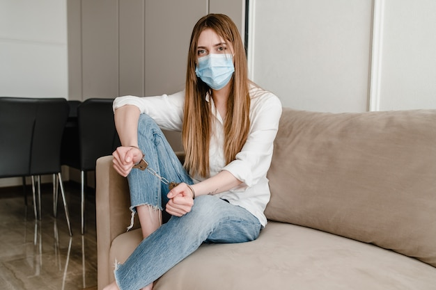 Woman with handcuffs at home on couch wearing mask. safety and security concept