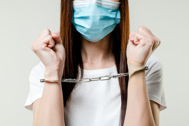 Woman with handcuffs wearing mask. quarantine concept