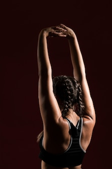 Woman with hands in air and dark background from behind shot