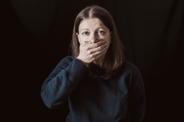 Woman with hands closed mouth. female violence . restriction and inability to speak.