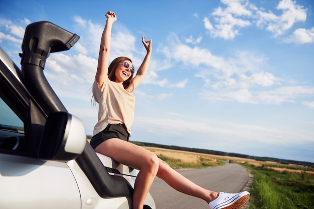 Woman with hands raised sitting on car