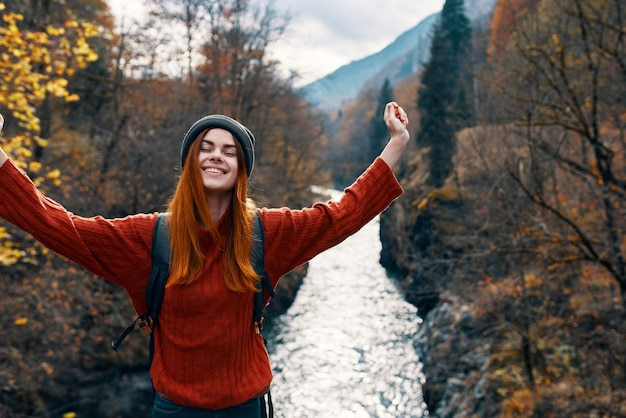 Woman with hands raised up on nature in the mountains autumn forest