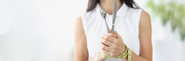 Woman with hands tied with measuring tape holding fork and knife closeup