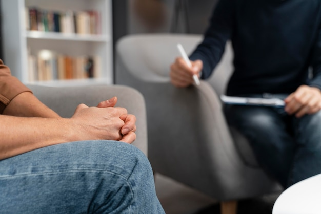 Woman with hands together talking with counselor