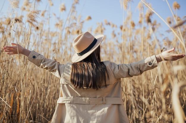 Женщина с поднятыми руками, наслаждаясь природой в поле камыша