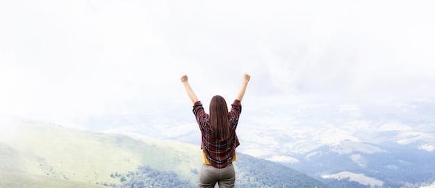 景色を楽しむ山の頂上に立って手を上げる女性自由の概念
