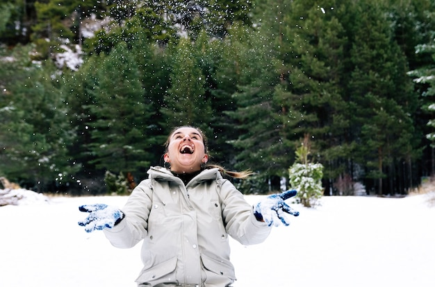 Woman with a happy face throwing snowflakes into the sky