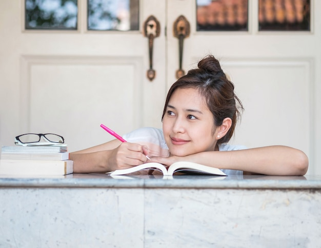 Woman with happy face with a book on marble table in front of house
