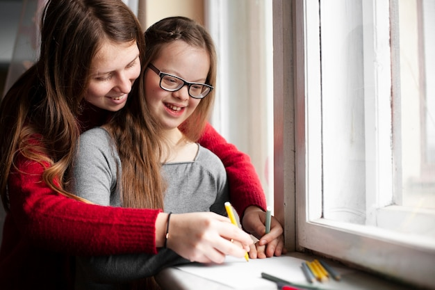 Woman with happy girl with down syndrome drawing