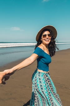 Woman with happy smile holding man hand and walking on beach