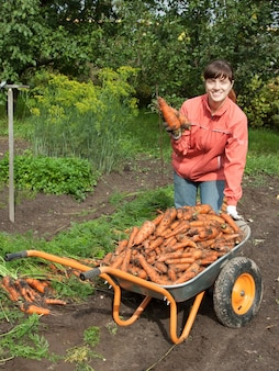 Woman with harvested carrot