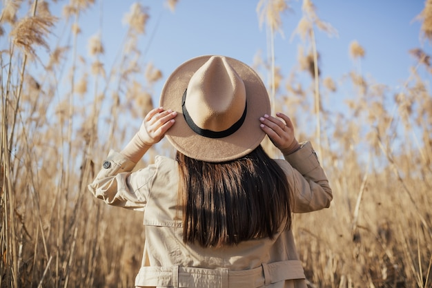 Женщина в шляпе на фоне голубого неба и высоких сухих тростников