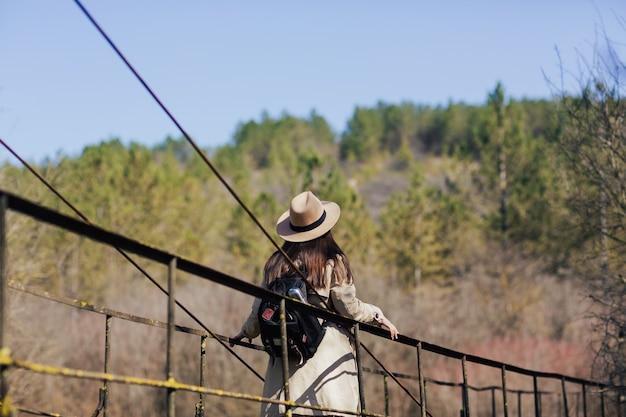 川に架かる吊橋の上を歩く帽子とバックパックを持つ女性