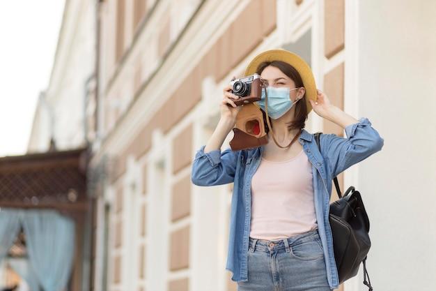 写真を撮る帽子とフェイスマスクを持つ女性