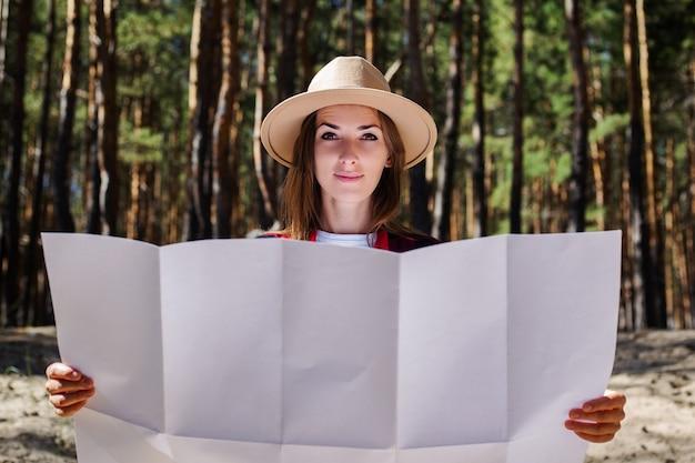 森の中で地図を持っている帽子と赤い格子縞のシャツを持つ女性。