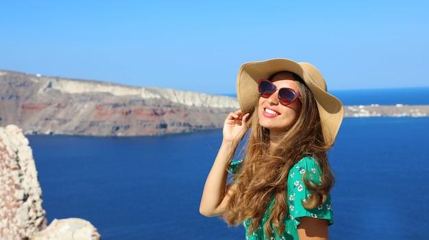 ギリシャのサントリーニ島で太陽を楽しんでいる帽子とサングラスを持つ女性
