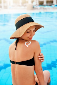 Woman with a hat on the edge of a pool applying sun cream with heart shape on tanned shoulder.