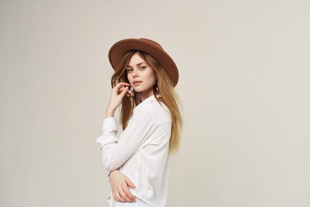 クローズアップの帽子ファッションストリートスタイルの服の白いシャツを持つ女性