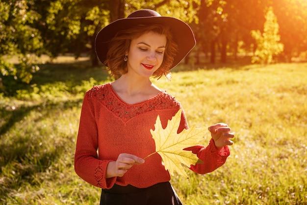 公園で黄色の葉を保持している帽子を持つ女性