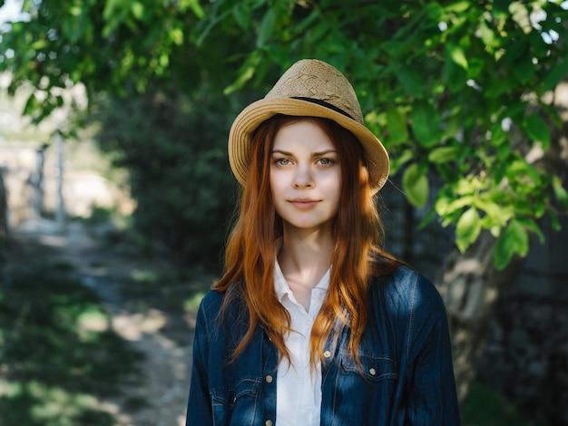 帽子をかぶった女性は屋外で木を散歩します。高品質の写真