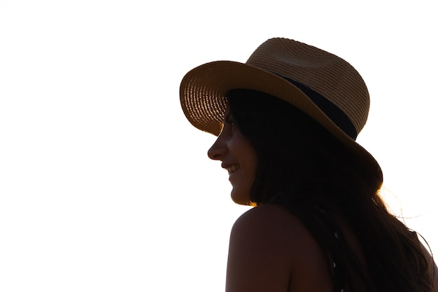 Woman with hat in profile looking at the horizon. copy space.