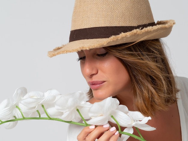 Woman with hat smells white flowers next to her face