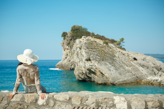 ビーチで時間を過ごす帽子を持つ女性