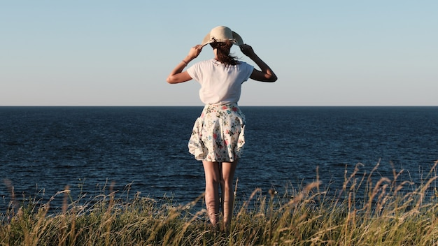 A woman with a hat stands on the shore. view from the back.