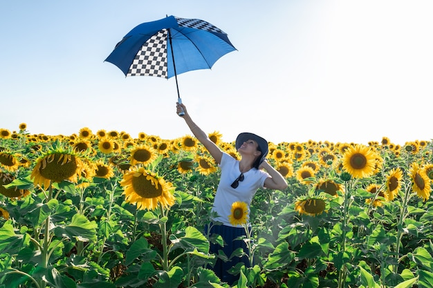 Woman with hat in a sunflower field with umbrella