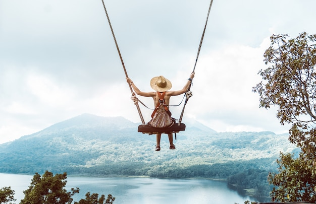 Woman with hat on a swing in bali