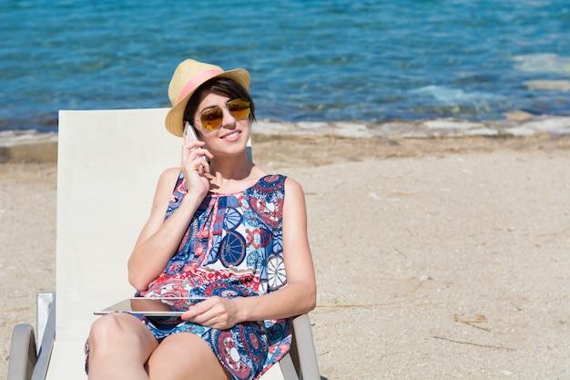 Donna con cappello comunica sul suo telefono