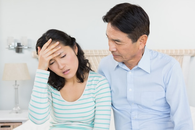 Woman with head ache sitting on bed with husband next to her