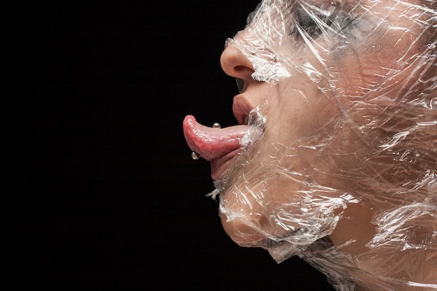 Woman with head covered in plastic and tongue out