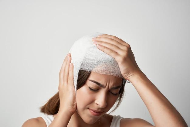 頭痛の包帯を巻いた頭の不快感のトラウマを持つ女性