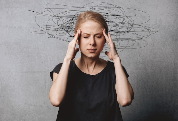 Woman with headache on grey space