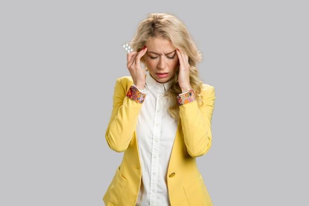 Woman with headache holding medicine