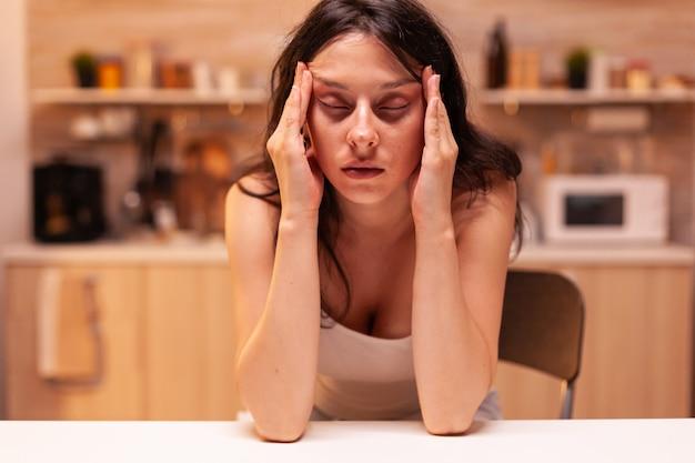 椅子に座っている頭痛のある女性。片頭痛、うつ病、病気、めまい症状で疲れ果てた不安感に苦しんでいるストレスの多い疲れた不幸な心配の体調不良の妻